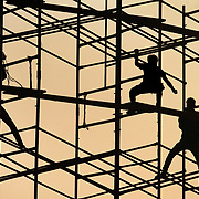 City workers deconstruct scaffolding  at the Gateway of India  on the shore of the Arabian Sea in south Mumbai, India. The metal structure was used from festival from the weekend before.<br />  Leica MP 240  135 mm