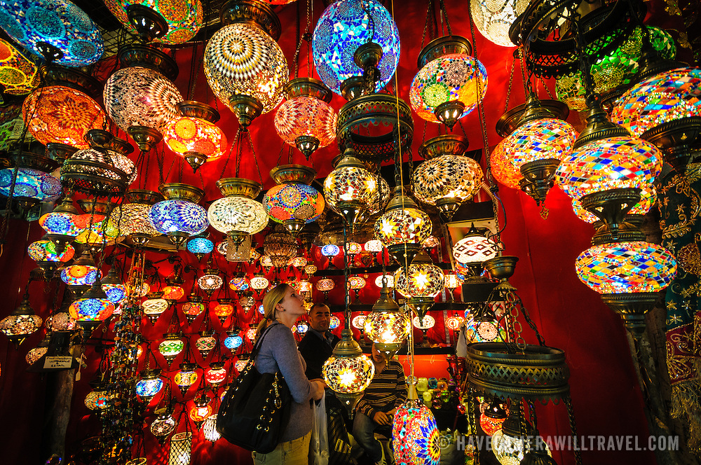 A shopkeeper shows a customer his wares. Istanbul's Grand Bazaar includes many stores selling brightly colored hanging lights with a teardrop design of colorful glass mosaics.