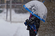 Middletown, New York -  A woman with an umbrella waits for a child at a bus stop during a snowstorm on Dec. 17. 2013.
