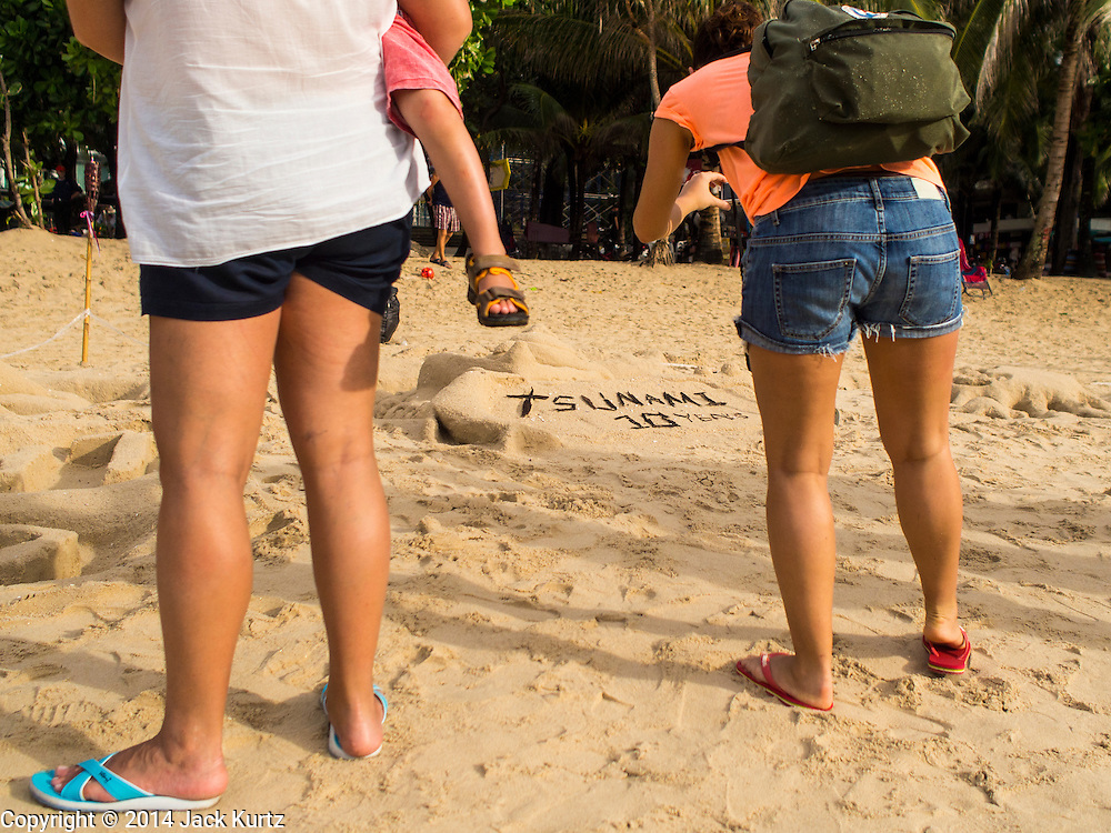 26 DECEMBER 2014 - PATONG, PHUKET, THAILAND:  Tourists walk past a memorial on the beach to mark the anniversary of the tsunami on Patong Beach in Patong, Phuket. Hundreds of people died in Patong and nearly 5400 people died on Thailand's Andaman during the 2004 Indian Ocean Tsunami that was spawned by an undersea earthquake off the Indonesian coast on Dec 26, 2004. In Thailand, many of the dead were tourists from Europe. More than 250,000 people were killed throughout the region, from Thailand to Kenya. There are memorial services across the Thai Andaman coast this weekend.   PHOTO BY JACK KURTZ