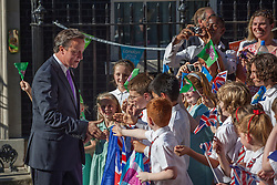 © licensed to London News Pictures. London, UK 26/07/2012. David Cameron meeting pupils as they wait for torch relay in Downing Street. Photo credit: Tolga Akmen/LNP