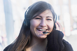Portrait of a young woman smiling talking on headset, Freiburg im Breisgau, Baden-Württemberg, Germany