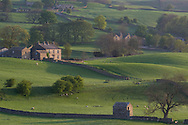 A house, stone barns and walls surrounded by fields on an early spring morning near Bainbridge, Wensleydale in The Yorkshire Dales National Park, Yorkshire, England, UK