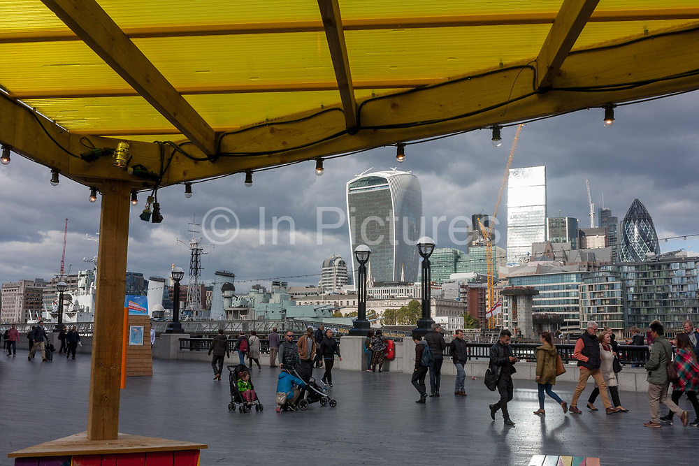 The yellow roof of a themed cafe promoting the capital as a Riviera, with a background panorama looking north from More London in Southwark, towards the City of London, on 6th October 2016, in London, England.