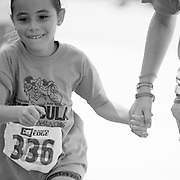 A young girl finishes the Missoula Kids Marathon holding the hand of her mother. Missoula Photographer