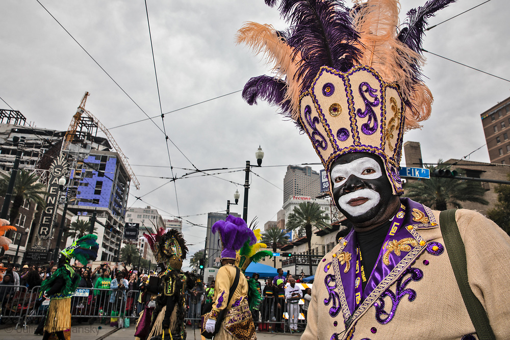 Zulu Parade participants in blackface on Mardi Gras  morning in New Orleans  near the partially collapsed Hard Rock Cafe  Hotel. The hotel collapsed while it was still underc construction  on Oct. 12, 2019, killing at least three workers. Two of the bodies remain trapped inside.