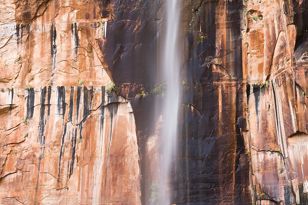 An ephemeral waterfall plunges down the giant red sandstone wall of Zion Canyon after a violent rainstorm in Zion National Park, Utah.