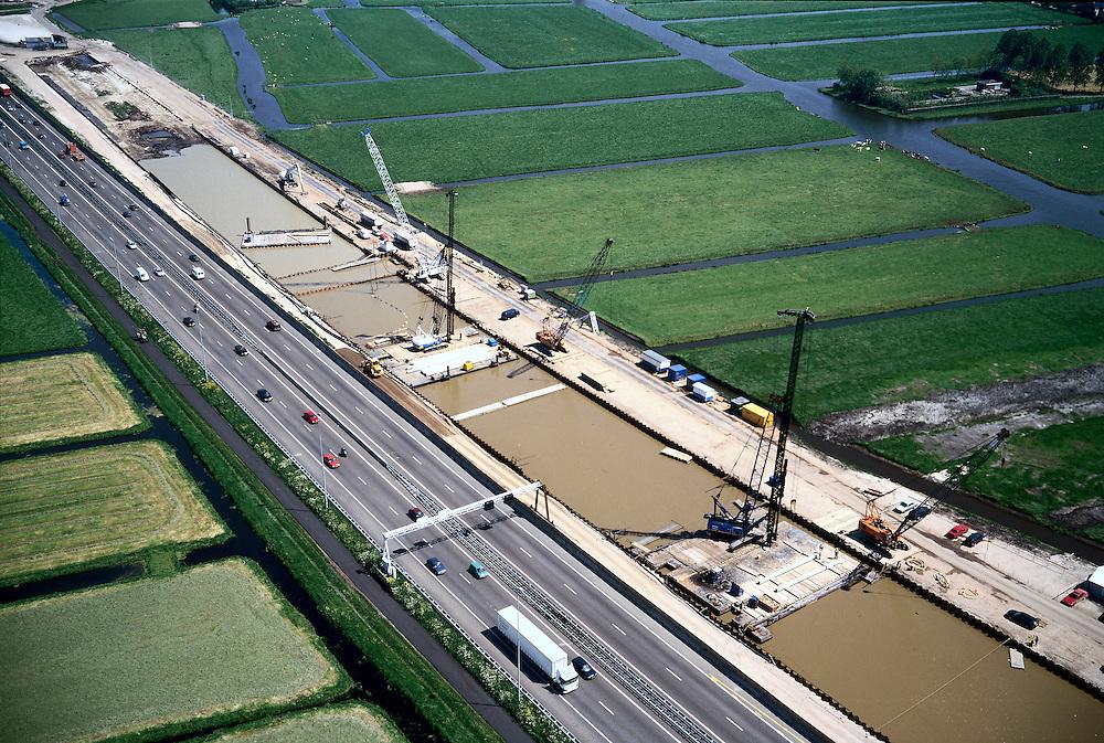 Nederland, Hoogmade, A4, 17-05-2002;kruising HSL en rijksweg A4; de autosnelweg (Schiphol _ Leiden) wordt verbreed terwijl de HSL de snelweg verdiept moet kruisen; bouwput met damwanden wordt uitgegraven, fundering wordt geheid, dan wanden van onderwater beton en leegpompen; infrastructuur, bouwen, spoor, rail, TGV planologie ruimtelijke ordening;<br /> luchtfoto (toeslag), aerial photo (additional fee)<br /> foto /photo Siebe Swart