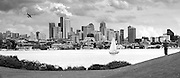 View of the downtown skyline and Lake Union from Gas Works Park in Seattle, Washington. A man looks out as a sailboat floats by and a sea plane flies towards the city.