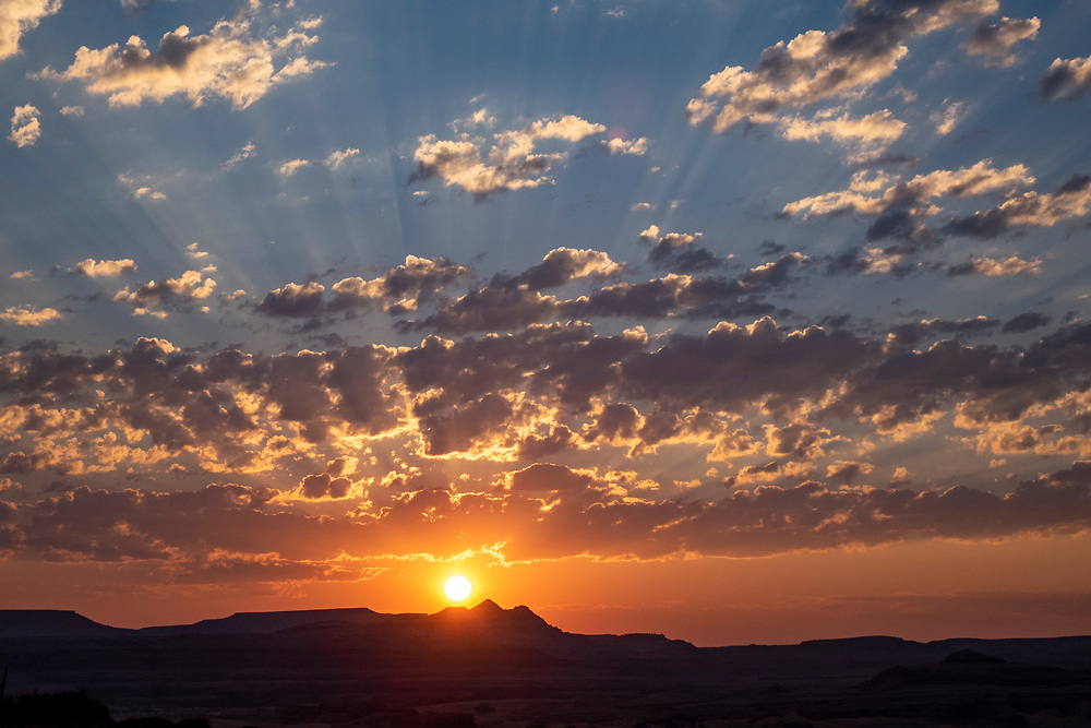 Sunrise in the Utah desert with shafts of sunlight going through the clouds