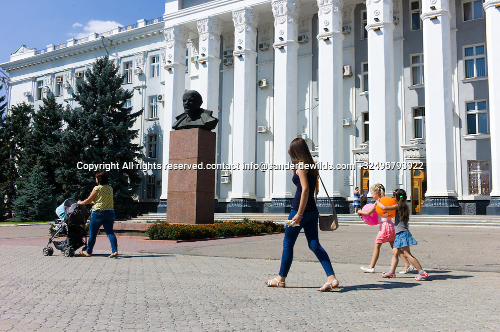 20150825  Moldova, Transnistria, Tiraspol. People passing the Statue head of Lenin in front of the Soviet House, city hall of the capitol of the self declared state Transnistria.