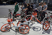 Young visitors to the capital sit on Santander rental bikes and wait at traffic lights next to a pile of Mobikes, on 13th May, in London, England.