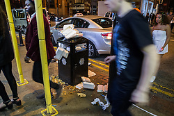 © Licensed to London News Pictures . 01/11/2015 . Manchester , UK . An overflowing litter bin outside a takeaway on Deansgate . Halloween revellers , wearing make up and costumes , out and about in Manchester City Centre . Photo credit : Joel Goodman/LNP