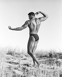male body builder posing on a sand dune in East Hampton, NY
