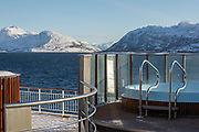 Hot tub on ship with view of mountain range covered in snow, Nesna, Norway