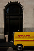 A DHL courier van makes a delivery and is parked in a side street in the City of London. Its yellow and red corporate branding is on the side of this small truck in Lombard Street, a narrow but very old medieval thoroughfare in the heart of London's oldest (financial) quarter where banks and insurance companies have their offices. DHL is a global market leader in the logistics industry and logistics company for the world. On the side of the van we see the words Express and Logistics with a high arch of an office address.