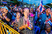 """15 NOVEMBER 2013 - BANGKOK, THAILAND: Thai protests dance during an anti-government protest in Bangkok. Tens of thousands of Thais packed the area around Democracy Monument in the old part of Bangkok Friday night to protest against efforts by the ruling Pheu Thai party to pass an amnesty bill that could lead to the return of former Prime Minister Thaksin Shinawatra. Protest leader and former Deputy Prime Minister Suthep Thaugsuban announced an all-out drive to eradicate the """"Thaksin regime."""" The protest Friday was the biggest since the amnesty bill issue percolated back into the public consciousness. The anti-government protesters have vowed to continue their protests even though the Thai Senate voted down the bill, thus killing it for at least six months.     PHOTO BY JACK KURTZ"""