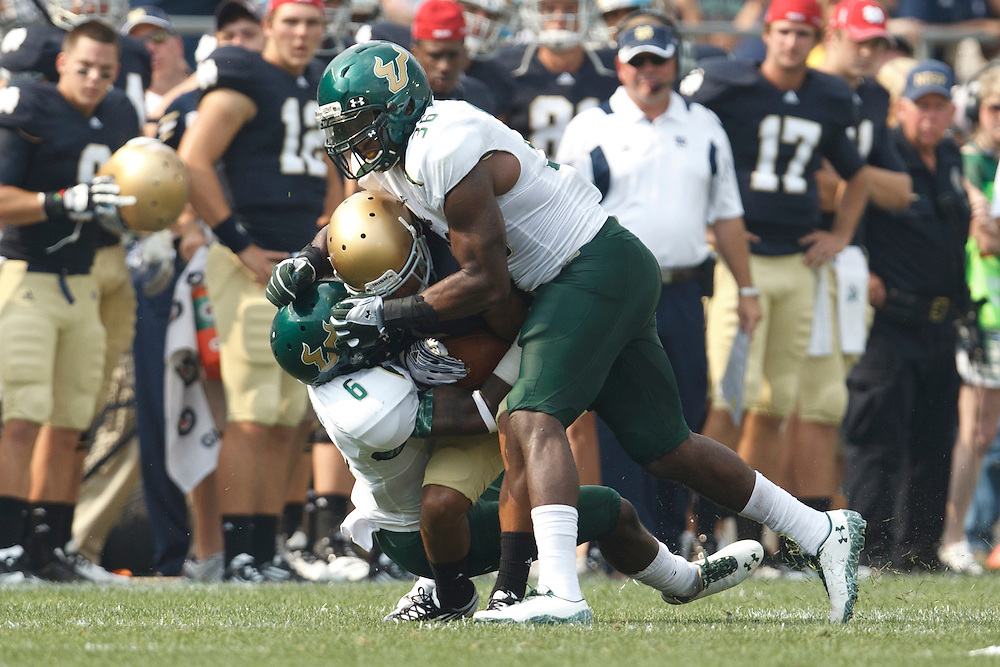 South Florida cornerback Kayvon Webster (#6) and linebacker Sam Barrington (#36) tackle Notre Dame receiver in action during NCAA football game between Notre Dame and South Florida.  The South Florida Bulls defeated the Notre Dame Fighting Irish 23-20 in game at Notre Dame Stadium in South Bend, Indiana.