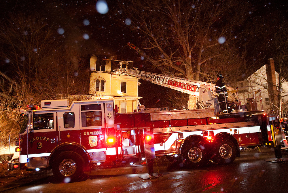 Newton, MA 02/21/2011.Snow falls as Newton firefighters work to extinguish a 4 alarm structure fire at 56 Waverly Ave in Newton early Monday morning.  One occupant was transported to Newton-Wellesley Hospital and another one remained unaccounted for, officials said..Alex Jones / For The Newton TAB
