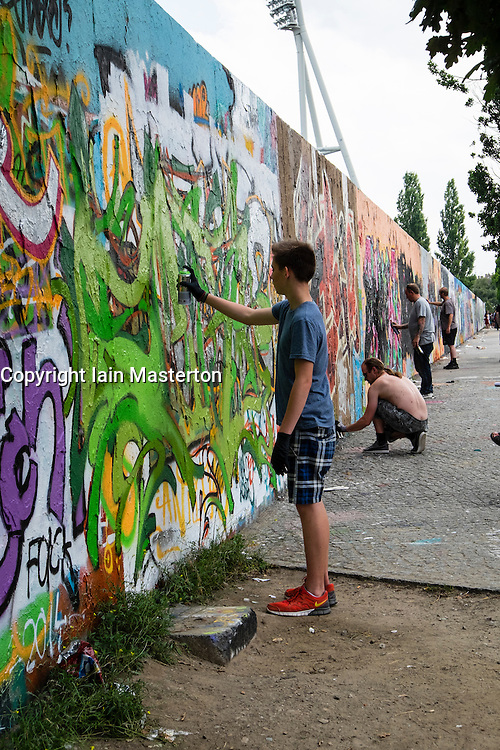 Graffiti artists spray painting a wall in Mauer Park in Prenzlauer Berg in Berlin Germany