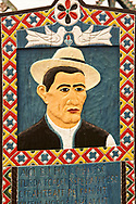 Tombstone of a man in traditional hat,  The  Merry Cemetery ( Cimitirul Vesel ),  Săpânţa, Maramares, Northern Transylvania, Romania.  The naive folk art style of the tombstones created by woodcarver  Stan Ioan Pătraş (1909 - 1977) who created in his lifetime over 700 colourfully painted wooden tombstones with small relief portrait carvings of the deceased or with scenes depicting them at work or play or surprisingly showing the violent accident that killed them. Each tombstone has an inscription about the person, sometimes a light hearted  limerick in Romanian. .<br /> <br /> Visit our ROMANIA HISTORIC PLACXES PHOTO COLLECTIONS for more photos to download or buy as wall art prints https://funkystock.photoshelter.com/gallery-collection/Pictures-Images-of-Romania-Photos-of-Romanian-Historic-Landmark-Sites/C00001TITiQwAdS8