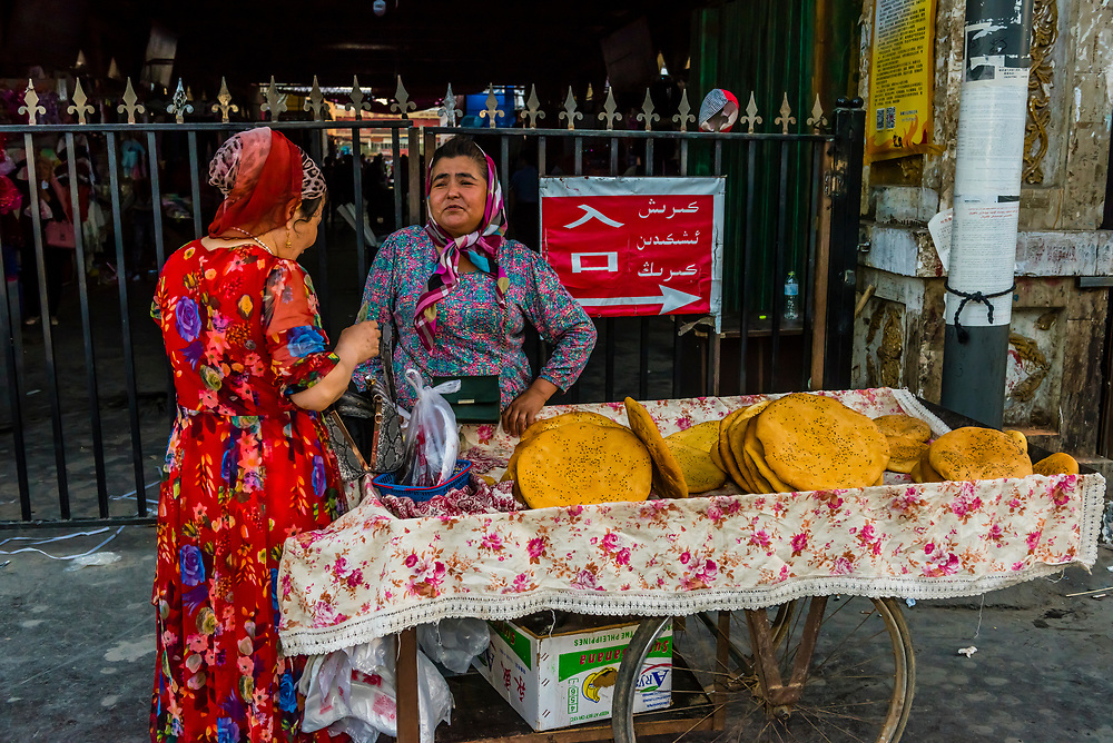 Uyghur woman selling nang (flatbread) at the street market outside the bazaar, Turpan, Xinjiang Province, China. Turpan is a small oasis town and former Silk Road outpost. Uyghur people are a Central Asian people of Muslim Turkic origin. They are China's largest minority group.