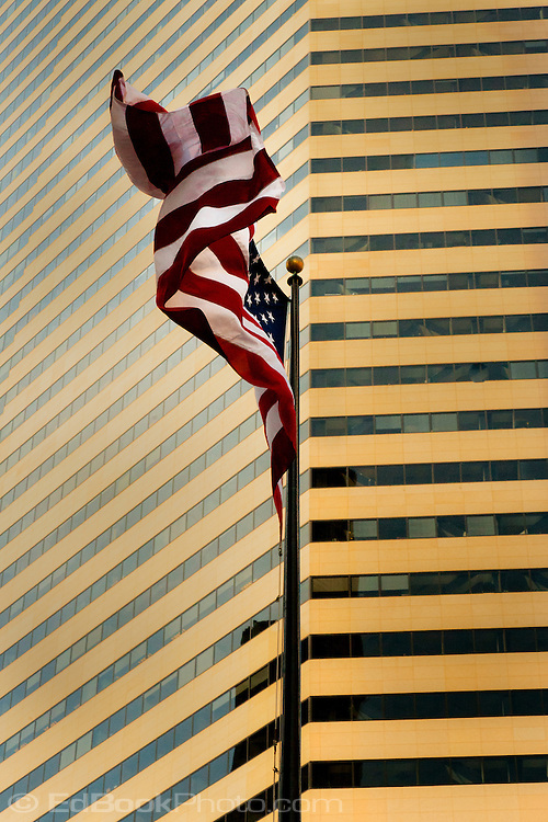 A US flag is flapping in the wind with a golden colored skyscraper filling the background, Seattle, WA, USA