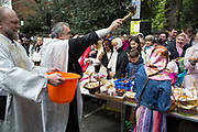 London, UK. Saturday 19th April 2014. Priest blesses the gathered people with a great deal of holy water. Easter celebration gathering at the Russian Orthodox Cathedral Church on Ennismore Gardens in West London. On this day before Easter Sunday Russians gather in a religious festival where their painted eggs; traditional cakes and other offerings are blessed. Then at midnight will be offered to God. Nothing is expected in retun in terms of good fortune.