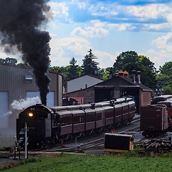 Strasburg, PA / USA - June 27, 2017:  A steam locomotive pulls passenger cars from the Strasburg Rail Road station.