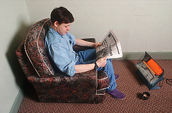 Teenage boy sitting in front of electric fire reading newspaper,