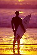 Male surfer on a beach in San Diego, CA.