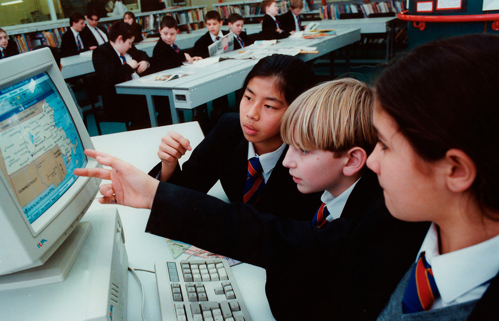 School pupils working at a computer; technology college; Dagenham; UK