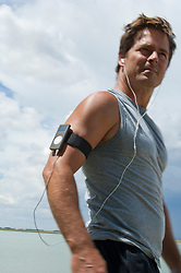 athletic man walking listening to his apple nano with earphones while standing by a lake
