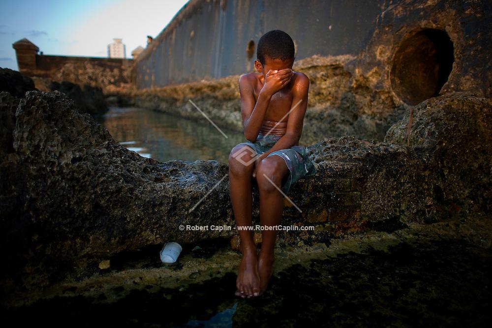 Cuban boy wipes face in water