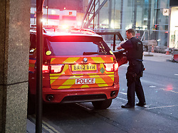 © London News Pictures. 30/04/2015. The police vehicle driving away from the A member of the Metropolitan police leaving a McDonald's restaurant in Victoria, London holding three drinks, while is colleagues wait in a police vehicle, parked on double yellow lines and using emergency lights. The police vehicle was blocking one lane of a busy road leading from Westminster through central Victoria. When the officer returned to the police vehicle the emergency lights were turned off. Photo credit: LNP