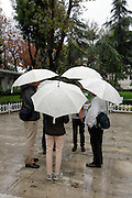 group of people together on a wet rainy day all with same umbrella