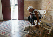 Madeline is bringing her dog Chespy in for treatment of parasites. Aniplant, Havana, Cuba.