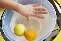 Child's hands washing fruit,