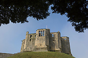 Part of Warkworth Castle, on 26th September 2017, in Warkworth, Northumberland, England. Although the settlement of Warkworth in Northumberland dates back to at least the 8th century, the first castle was not built until after the Norman Conquest. The town and its castle occupied a loop of the River Coquet. The castle was built at the south end of the town, guarding the narrow neck of the loop. A fortified bridge also defended the approach to the town