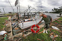 """With tropical force gusts of winds still blowing Phillip Elzas, 49, picks up the life preserver of the boat """"Easy Life,"""" a trawler that sunk at Sundance Marine in Palm Shores, Fla. on Monday, September 11, 2017 after Hurricane Irma blew through Brevard. Photo by Orlando Sentinel/TNS/ABACAPRESS.COM"""