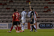 Referee Craig Hicks shows a yellow card to Shrewsbury Town Midfielder Oliver Norburn during the EFL Sky Bet League 1 match between Lincoln City and Shrewsbury Town at Sincil Bank, Lincoln, United Kingdom on 15 December 2020.