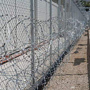 The double barbed wire fence surrounding the First Reception Centre (Hot-Spot) of Leros, Greece.<br /> <br /> The Hot Spot in Lepida opened on the 26th of February 2016 in the grounds of the former Lepida psychiatric hospital.  At the beginning it served as a registration camp for refugees and migrants who were travelling to Europe through Greece but since the closure of the borders in March 2016 it serves as a permanent camp. People are allowed to go out, they have three meals a day, the prefabricated huts have a bathroom and are air-conditioned and compering to other refugee camps in Greece the conditions are bearable.