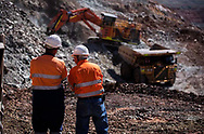 Workers watch an ore truck being loaded at an open pit mine in the Pilbara.