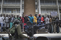November 18, 2017 - Harare, Zimbabwe - Protesters demanding President Mugabe stand down, look up and cheer as an army helicopter flies over the crowd, as they gather in front of an army cordon on the road leading to State House in Harare. In a euphoric gathering that just days ago would have drawn a police crackdown, crowds marched through Zimbabwe's capital on Saturday to demand the departure of President Mugabe, one of Africa's last remaining liberation leaders, after nearly four decades in power. (Credit Image: © Belal Khaled/NurPhoto via ZUMA Press)