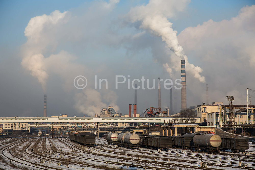 A view of the train yard as water vapor and smoke rise from a Tonghua Iron & Steel Group Co. plant in the distance in the Erdaojiang district in Tonghua, Jilin province, China, on Wednesday, Jan. 6, 2016. The citys once-vaunted state-run steel mills have slipped inexorably into decline, weighed down by slumping global markets, a changing economy, and the burden of costs and responsibilities to the people of the town they fostered. Previous attempts to privatise the enterprise have met with stiff resistance, one such attempt resulted the mob lynching and death of a private businessman who wanted to invest and streamline the operation.