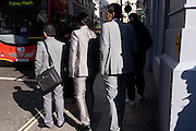 Three men in decreasing sizes wearing matching grey suits are about to cross a busy street in central London.