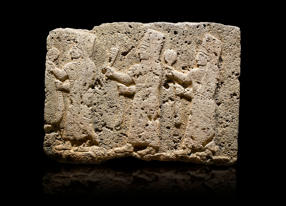 Hittite monumental relief sculpted orthostat stone panel of a Procession Limestone, Karkamıs, (Kargamıs), Carchemish (Karkemish), 900-700 B.C. Anatolian Civilisations Museum, Ankara, Turkey.<br /> <br /> It is a depiction of three marching female figures in long dress with a high headdress at their head. These women are considered to be the nuns of the Goddess Kubaba. The figures in the front and behind have a round mirror in their right hand while the figure in the middle has a bunch of spica in her right hand. Figures carry objects similar to a sceptre in their left hand.  <br /> <br /> Against a black background. .<br />  <br /> If you prefer to buy from our ALAMY STOCK LIBRARY page at https://www.alamy.com/portfolio/paul-williams-funkystock/hittite-art-antiquities.html  - Type  Karkamıs in LOWER SEARCH WITHIN GALLERY box. Refine search by adding background colour, place, museum etc.<br /> <br /> Visit our HITTITE PHOTO COLLECTIONS for more photos to download or buy as wall art prints https://funkystock.photoshelter.com/gallery-collection/The-Hittites-Art-Artefacts-Antiquities-Historic-Sites-Pictures-Images-of/C0000NUBSMhSc3Oo