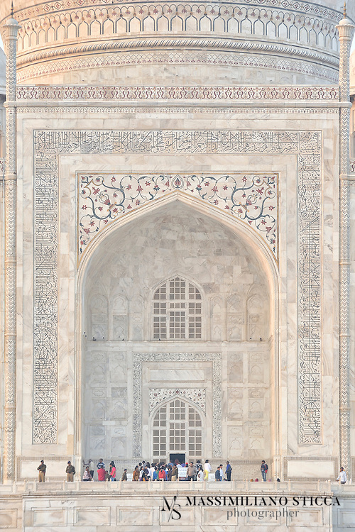 """The Main Gate of the Taj Mahal with the calligraphy..The calligraphy on the Great Gate reads """"O Soul, thou art at rest. Return to the Lord at peace with Him, and He at peace with you."""".The calligraphy was created by a calligrapher named Abdul-Haq, in 1609. Shah Jahan conferred the title of """"Amanat Khan"""" upon him as a reward for his """"dazzling virtuosity"""".[8] Near the lines from the Qur'an at the base of the interior dome is the inscription, """"Written by the insignificant being, Amanat Khan Shirazi."""" Much of the calligraphy is composed of florid thuluth script, made of jasper or black marble, inlaid in white marble panels. Higher panels are written in slightly larger script to reduce the skewing effect when viewed from below. The calligraphy found on the marble cenotaphs in the tomb is particularly detailed and delicate."""