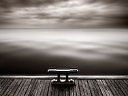 """A cleat on a deck at the lake of Viverone in Piedmont, Italy. Taken at sunset on a evening at the beginning of February. This picture is a composite of two different exposures: 2 seconds for the water and about 40"""" for the sky."""