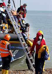 © Licensed to London News Pictures. 22/09/2021. Dungeness, UK. A young girl is helped ashore at Dungeness in Kent after being rescued by the RNLI as she crossed the English Channel. Hundreds of migrants have made the crossing in the calm weather this week. Photo credit: Sean Aidan/LNP